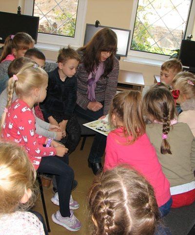 Bibliotekininkė vaikams skaito pasaką