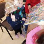 """Vaikai tyrinėja knygelę """"Nušviestas pasaulis"""""""