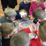 Vaikai tyrinėja knygą su spalvotais akiniais