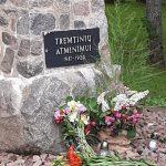 Prie paminklo padėtos gėlės ir uždegtos žvakutės