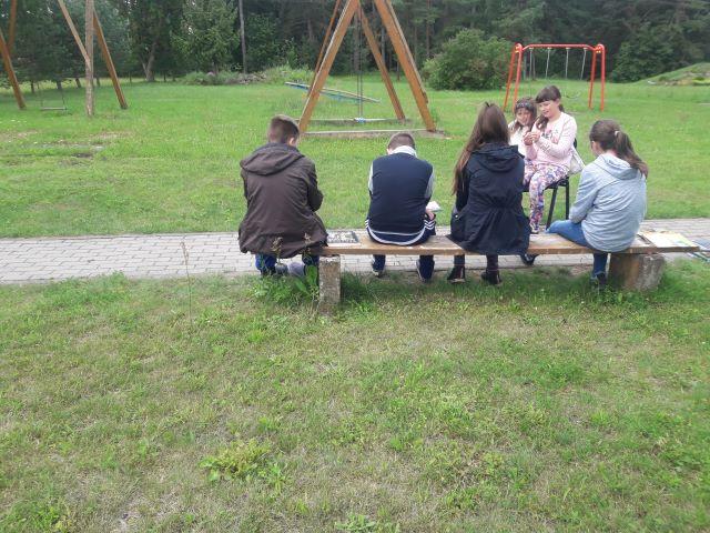 Renginio dalyviai skaito knygas Užlieknės bendruomenės kiemelyje