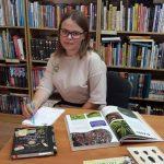 Bibliotekos savanorė Rugilė ieško knygose informacijos, kurią panaudos kuriant užduotis žaidimui