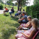 """Vaikai klausosi istorijų iš skaitomos knygelės """"Peliūnės vasara"""""""