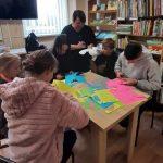 Bibliotekininkė pasakoja vaikams apie vitražo techniką